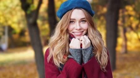 boina : Close up view of Smiling brunette woman in beret hat and coat looking at camera while walks in park