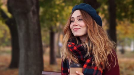 boina : Close up view of Smiling brunette woman in beret hat and coat drinking coffee while sitting on bench in park Archivo de Video