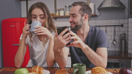 jeść : Happy lovely couple having breakfast and using smartphones while sitting together on kitchen