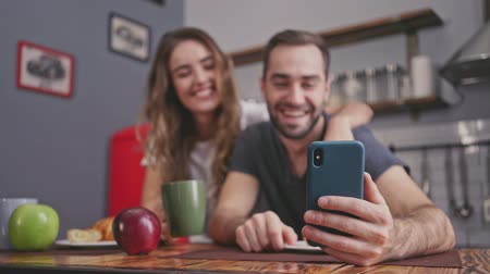 video making : Happy lovely couple having breakfast and making selfie on smartphone while sitting together on kitchen Stock Footage