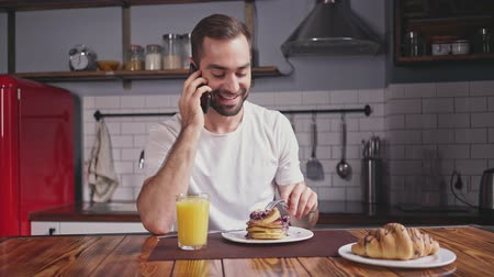 utensílios : Smiling handsome bearded man having breakfast and talking by smartphone while sitting by the table at home
