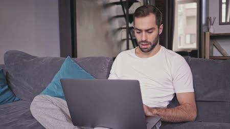 предназначенный только для мужчин : Serious handsome bearded man using laptop computer while sitting on sofa at home
