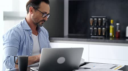 genius : Smiling pensive mature man in shirt and eyeglasses sitting by the table and working with laptop computer and documents at home