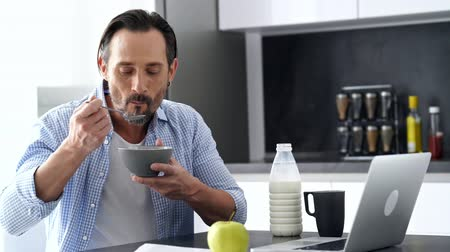 genius : Happy mature man in shirt sitting by the table with laptop computer while having breakfast at home