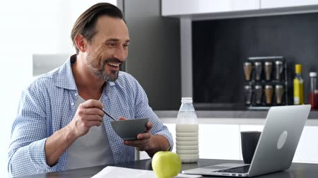 zseni : Side view of Pleased mature man in shirt sitting by the table with laptop computer while having breakfast at home