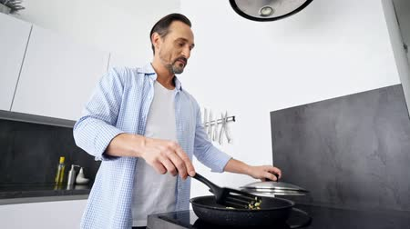 aşağıda : Smiling concentrated mature man cooking breakfast while standing at the kitchen at home
