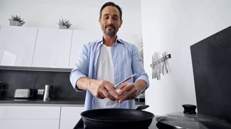 холостяк : Happy mature man cooking breakfast while standing at the kitchen at home