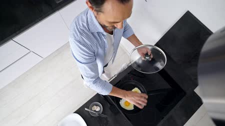 agglegény : Top view of mature man cooking breakfast while standing at the kitchen at home