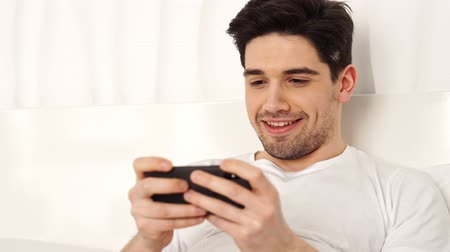 laying : Concentrated brunette smiling man wearing casual clothes playing game on smartphone and win while lying in bed