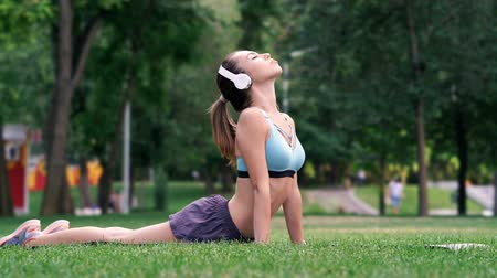 eklemek : Young sportswoman in headphones doing fitness exercise while being in park Stok Video