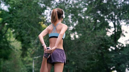 прослушивание : Back view of Young sportswoman in headphones warming up while being in park