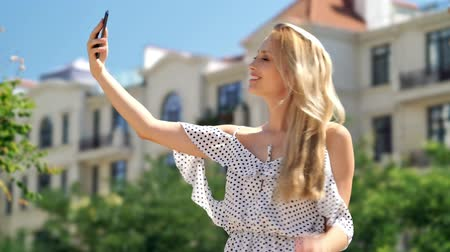 vay : Happy blondy woman in dress making selfie on smartphone while standing at park