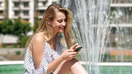 vay : Side view of pleased blondy woman in dress using smartphone while sitting near the fountain at park