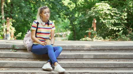 fones de ouvido : Calm pretty students woman waiting someone with cup of coffee while sitting on stairs outdoors