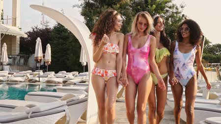 companionship : Group of Beauty women friends in swimsuits having fun together while walking near the swimming pool outdoors