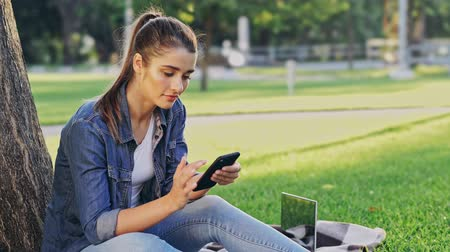 field study : Happy brunette woman using smartphone while sitting near the tree on grass in park Stock Footage