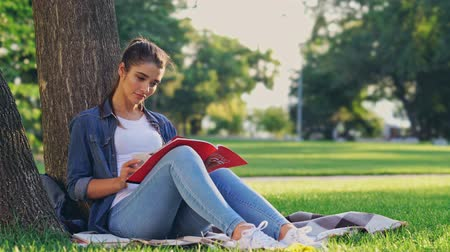 field study : Smiling brunette woman reading magazine and writing something while sitting near the tree on grass in park
