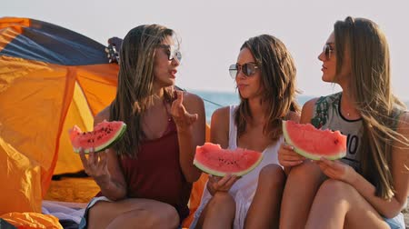кемпинг : Group of happy friends eating watermelon and having fun time together at beach near the sea
