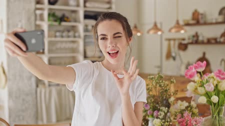 bueno : Attractive young brunette woman in white t-shirt taking a selfie photo on smartphone standing at the dining room Archivo de Video