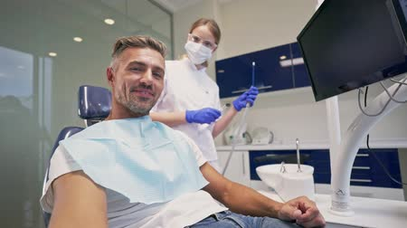 stomatologia : Attractive smiling man taking a selfie photo while dentist preparing and trying to start dental procedure at the dental clinic Wideo