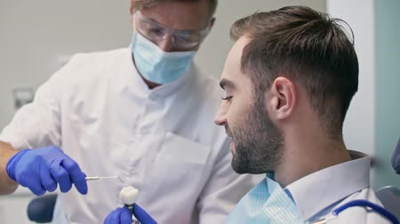 manequim : Close up view of Serious brunette man listening dentist about problem with his tooth and looking at the dummy tooth before dental procedure at the dental clinic Stock Footage