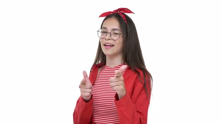 saç bantı : Smiling young girl in red shirt pointing to you with fingers and winking while looking at the camera over white background isolated Stok Video