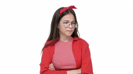 resentment : Upset young brunette girl in red shirt with resentful look and crossed hands while looking at the camera over white background isolated