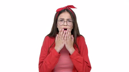 headband : Serious young brunette girl in red shirt becoming surprised and shocked from getting some bad news while looking to the camera over white background isolated