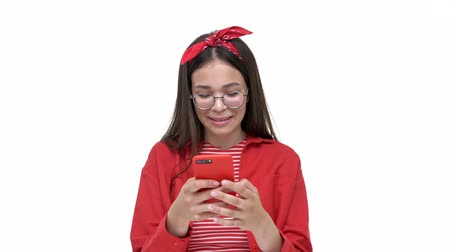 headband : Pretty young brunette girl in red shirt smiling and laughing while chatting on smartphone over white background isolated