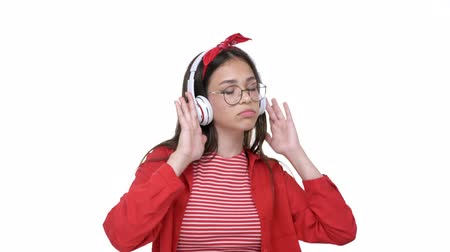 язык : Cheerful young brunette girl in red shirt listening music on wireless earphones and dancing over white background isolated