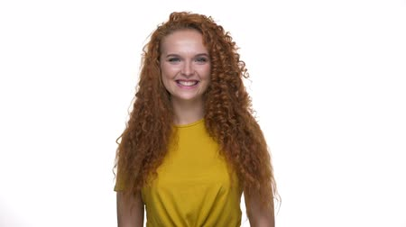 accepting : Cheerful young redhair curly lady agreeing with something and shaking her head looking at the camera over white background isolated