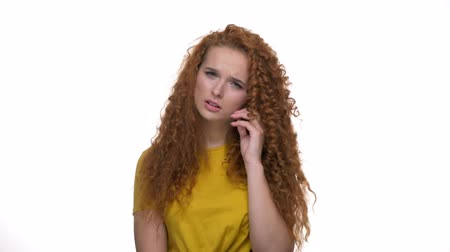 ruivo : Upset young redhead curly lady shaking head and touching her face because of worrying about something while looking at the camera over white background isolated Stock Footage