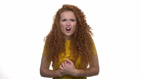 гримаса : Upset young redhead curly lady becoming shocked and feeling pain in her chest because of getting some bad news while looking at the camera over white background isolated