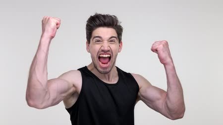 vzrušený : Excited young bearded sporty man in black shirt screaming and making winner gesture while looking at the camera over gray background isolated Dostupné videozáznamy