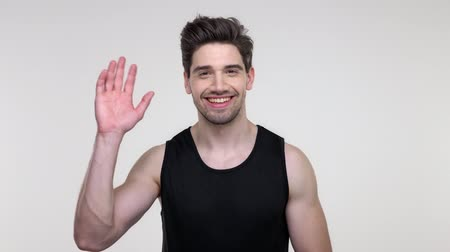 köszönt : Smiling young bearded sporty man in black shirt waving a hand to the camera over gray background isolated