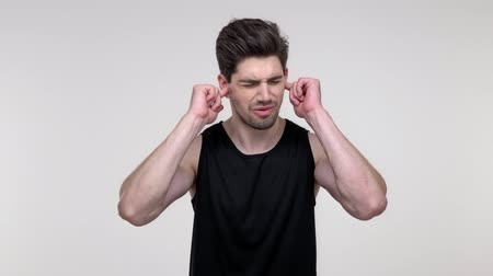 errado : Displeased young bearded sporty man in black shirt shaking his head and closing his ears with fingers because of noise while looking at the camera over gray background isolated