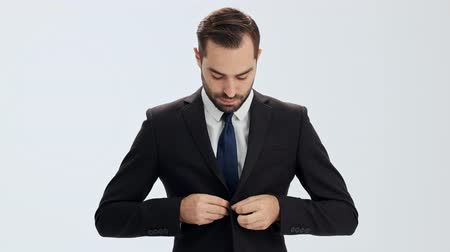 buttoning : Serious young businessman in black suit and blue tie making few steps and buttoning his jacket while looking at the camera over gray background isolated
