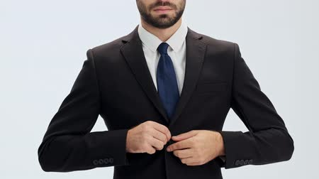 close cropped : Cropped view of serious young businessman in black suit and blue tie buttoning his jacket and putting his hands in pockets over gray background isolated
