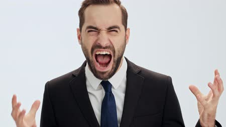 cavalheiro : Close up view of angry young businessman in black suit and blue tie screaming and gesturing with hands while looking at the camera over gray background isolated