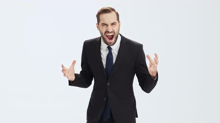 hate : Emotional young businessman in black suit and blue tie becoming very angry and screaming loudly gesturing with hands while looking at the camera over gray background isolated Stock Footage