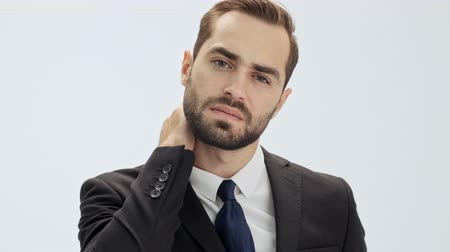 gentleman : Upset young businessman in black suit and blue tie massaging his neck because of neckache while looking at the camera over gray background isolated
