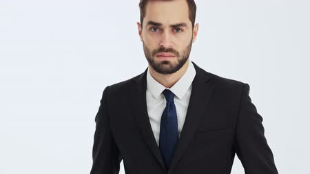 miserável : Handsome young businessman in black suit and blue tie feeling sad and crying while looking at the camera over gray background isolated Stock Footage