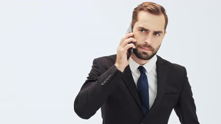 call out : Serious young businessman in black suit and blue tie taking his smartphone out of the pocket and becoming angry and disappointed while having a call over gray background isolated
