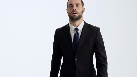 пальто : Serious young businessman in black suit and blue tie walking to the camera and stumbled over gray background isolated
