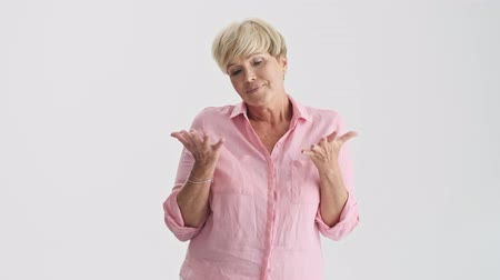 amadurecer : Doubtful blonde senior woman thinking about something and shaking her head while gesturing with hands looking at the camera over gray background isolated