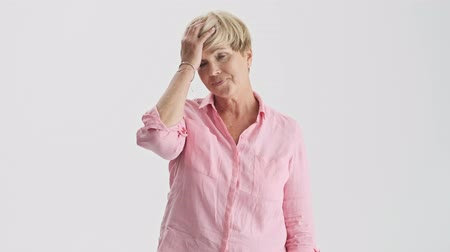 head over : Disappointed blonde elderly woman shaking her head negatively and touching her head with hand while looking at the camera over gray background isolated
