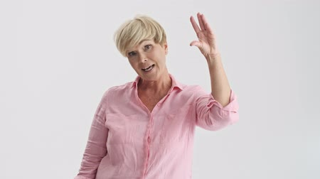 fazla : Attractive blonde old woman making bla-bla gesture with hand to someone who is talking too much while looking at the camera over gray background isolated Stok Video