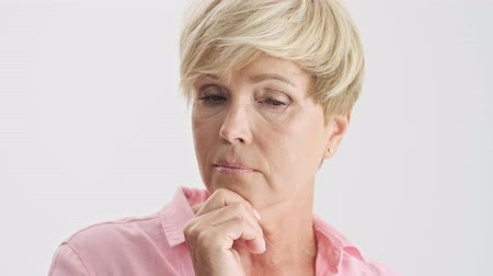 elliler : Cropped view of thoughtful blonde old woman looking around and touching her chin and ear over gray background isolated
