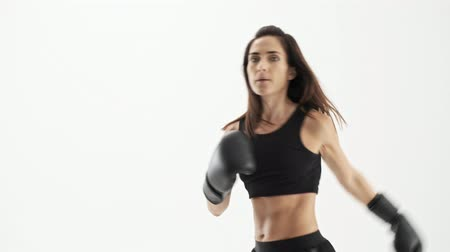 puncs : Active cute sporty brunette woman in black sportswear with the black gloves boxing while looking at the camera over white background isolated