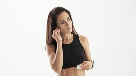 caso : Calm cute sporty brunette woman in black sports bra getting wireless earphones out from the case and putting them on over white background isolated Vídeos
